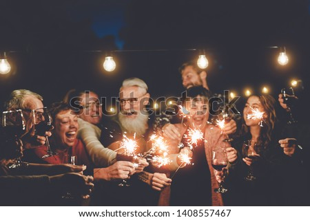 Happy family having at dinner party outdoor - Group of multiracial older and young people celebrating together drinking wine holding fireworks sparklers - Concept of youth and elderly parenthood #1408557467