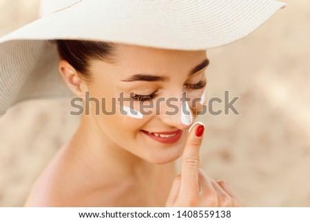Beautiful Woman Face Portrait Beauty Skin Care Concept. Suncream. Suntan Lotion Beautiful Woman Applying on beautiful on Face. Sunscreen Solar Cream. Sun protection.The Girl Uses  Moisturizer Sunblock #1408559138