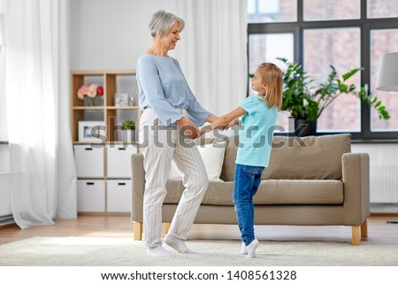family, generation and people concept - happy smiling grandmother and granddaughter having fun at home #1408561328