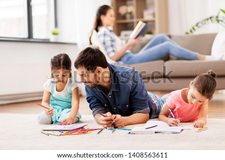 family, fatherhood and leisure concept - father spending time with his little daughters drawing in sketchbooks by crayons and lying on floor at home #1408563611
