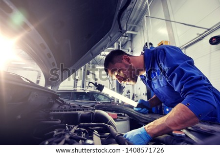 car service, repair, maintenance and people concept - auto mechanic man with lamp working at workshop #1408571726