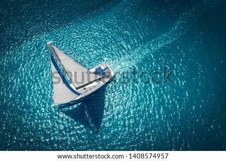 Regatta sailing ship yachts with white sails at opened sea. Aerial view of sailboat in windy condition. Royalty-Free Stock Photo #1408574957