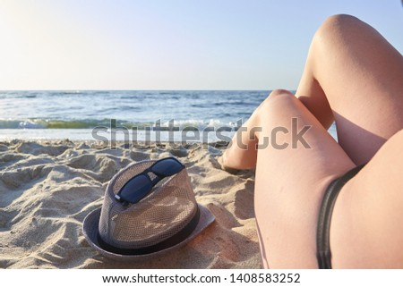Beautiful woman's legs on the beach and sea background #1408583252