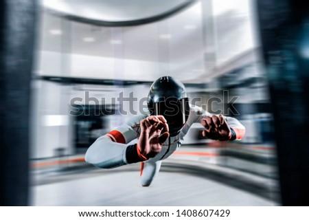 Levitation in wind tunnel. Indoor sky diving. Team flyers. Yoga fly in wind tunnel. Indoor skydiving.  #1408607429