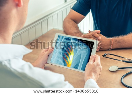 Doctor holding a digital tablet with x-ray of the chest of the patient with pain in the ribs #1408653818