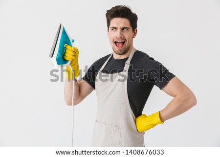Photo of european young man wearing yellow rubber gloves for hands protection smiling and holding iron while cleaning house isolated over white background