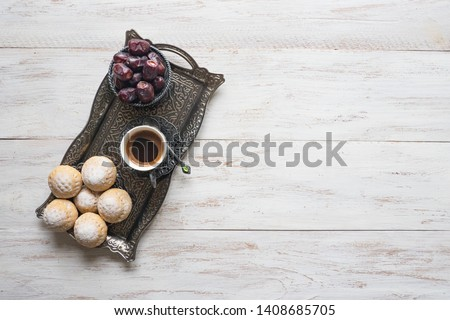 Top view on silver plate with sweets, date fruits and coffee cup on the white wooden table. Ramadan background.
