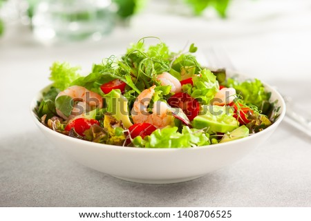 Fresh summer salad with shrimp, avocado and tomato cherry in bowl on light table. Concept of healthy eating. #1408706525