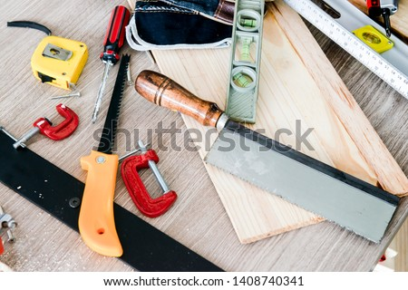 saw,small piece of wood,electric screwdriver,spirit level,plank,wood,measurement,level tools,tape measure,plank wood,sawing the wood, C-clamp,G-clamp,woodwork,instruments on table for carpentry. #1408740341