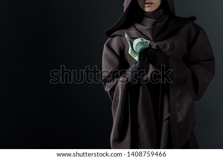 cropped view of woman in death costume holding euro banknotes isolated on black #1408759466