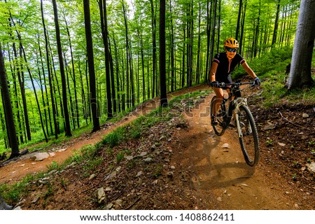 Mountain biking woman riding on bike in autumn mountains forest landscape. Woman cycling MTB flow trail track. Outdoor sport activity. #1408862411