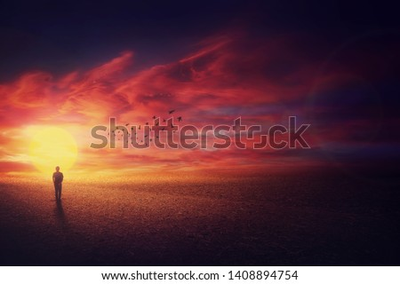 Surreal scenery view as a wanderer guy silhouette walking in front of beautiful sundown background and a flock of birds flying up in the sky. Life journey concept. #1408894754