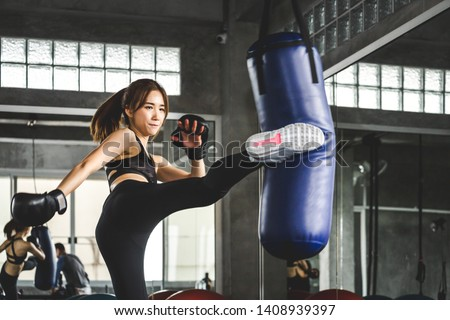 Young asian athlete woman with boxing gloves doing kick boxing training in sport gym #1408939397