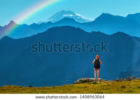Girl traveler with backpack stands on a stone back to the viewer. She looks at the snow-capped top. Picturesque cloudless landscape with a rainbow. Wallpaper for concept of business thinking. #1408963064