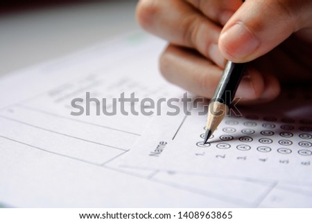 Students hand holding pencil writing selected choice on answer sheets and Mathematics question sheets. students testing doing examination. school exam #1408963865