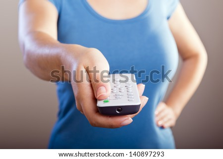 Woman holds a remote control in her hands with her body out of focus #140897293