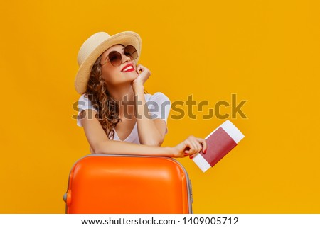 concept of travel. happy woman girl with suitcase and passport on  yellow colored background #1409005712