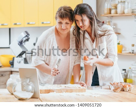 Women making pastries. Mother daughter looking at tablet. Recipe cooking class course online. Home baking hobby fun. #1409051720