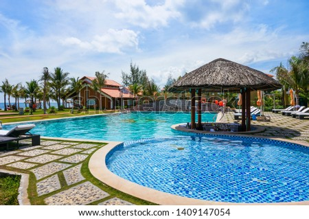 PHU QUOC ISLAND, VIETNAM - MAY 4,2013: Swimming pool at the beach resort in Phu Quoc island in Vietnam. This is a relaxing area of the resort. #1409147054