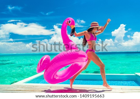 Vacation fun woman in bikini with funny inflatable pink flamingo pool float running of joy jumping by infinity swimming pool. Girl enjoying travel holidays at resort luxury overwater bungalow travel. #1409195663