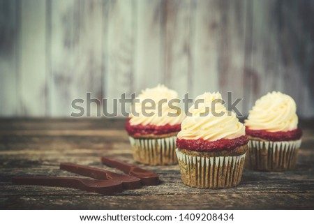 Cupcakes with whipped vanila cream, on wooden table. Picture for a menu or a confectionery catalog. Copy space. Sweet cupcakes for your greetings and birthday party.