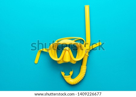 flat lay shot of yellow diving mask with snorkel over turquoise blue background. minimalist photo of dive mask and snorkel with central composition #1409226677