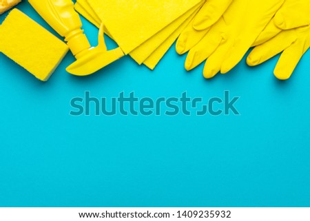 yellow cleanser in plastic container with spray, rubber protective gloves, sponge and cloths for cleaning on the turquoise blue background. flat lay image of yellow cleaning products with copy space #1409235932
