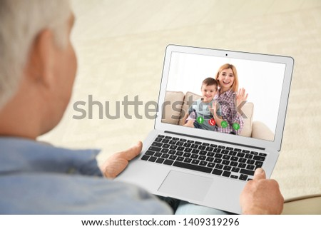 Closeup view of senior man talking with family members via video chat at home  #1409319296