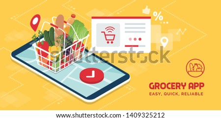 Grocery delivery at home and smartphone app: full shopping basket with fresh vegetables, food and beverage on a mobile phone display #1409325212