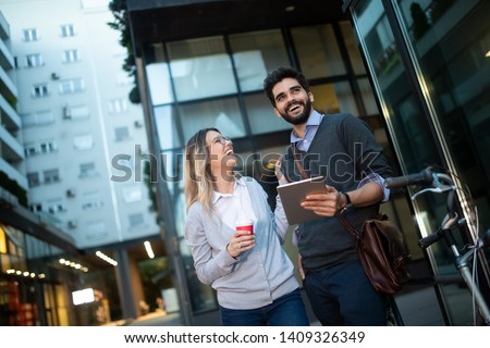 Beautiful young couple walking down the street with tablet #1409326349