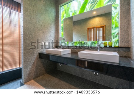 Luxury bathroom features basin, toilet in the house or home building #1409333576