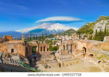 Ruins of Ancient Greek theatre in Taormina on background of Etna Volcano, Italy. Taormina located in Metropolitan City of Messina, on east coast of island of Sicily. #1409337758