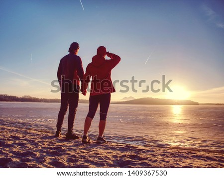Couple runners running in winter nature. Frozen river beach run. Copy space. #1409367530