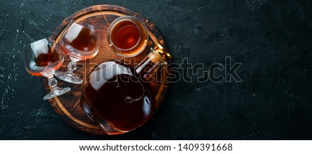 A bottle of cognac and glasses on a black background. Brandy. Top view. Free space for your text. Royalty-Free Stock Photo #1409391668