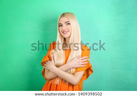 Portrait of beautiful smiling woman on color background #1409398502