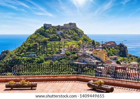 Taormina Castle, known as Castello di Taormina or Castello Saraceno, and little church of Madonna della Rocca located on green mount in Messina province on Sicily island in Italy.   Royalty-Free Stock Photo #1409449655