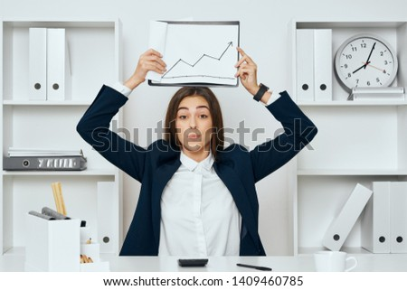Woman with a finance folder over her head calculator glasses pencils room with racks                          #1409460785