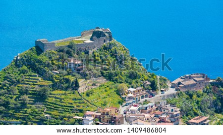 Taormina Castle, known as Castello di Taormina or Castello Saraceno, and little church of Madonna della Rocca located on green mount in Messina province on Sicily island in Italy.   Royalty-Free Stock Photo #1409486804
