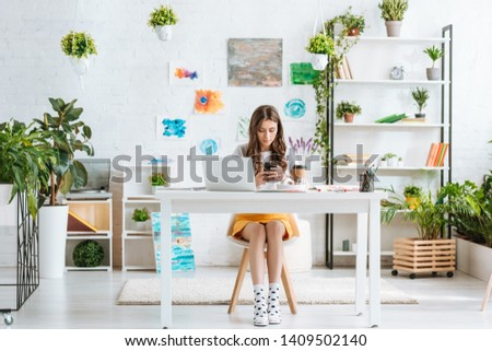 pretty young woman using smartphone while sitting in spacious room with green plants and paintings on wall #1409502140