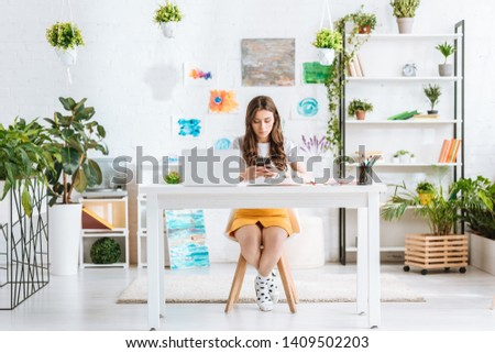 young woman using smartphone while sitting at desk with laptop in spacious room at home #1409502203