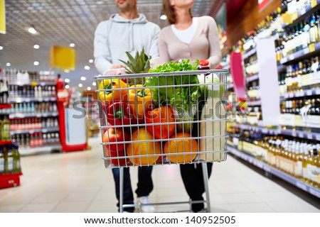 Image of cart full of products in supermarket being pushed by couple #140952505