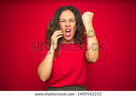 Middle age senior woman talking on the phone over red isolated background annoyed and frustrated shouting with anger, crazy and yelling with raised hand, anger concept #1409542253