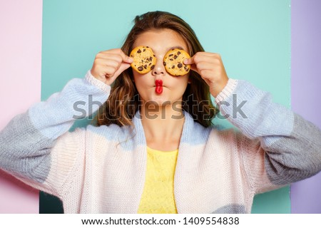 My favorite cookies. Pretty girl covering eyes with cookies. Bakery style chocolate chip cookie recipe. Cute girl having fun with cookies. Following a cooking recipe. Bakery shop. #1409554838