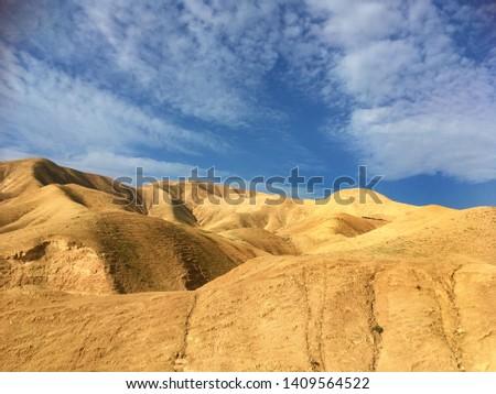 distant goat herd on desert sands beneath a vast sky near Jerusalem Israel #1409564522
