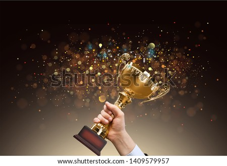 Man holding up a gold trophy cup with abstract shiny background, copy space for text Royalty-Free Stock Photo #1409579957