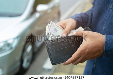 Businessman Person holding a wallet in the hands of take money out of pocket stand front car prepare pay by installments - insurance, loan and buying car finance concept insurance, payment a car Royalty-Free Stock Photo #1409587127