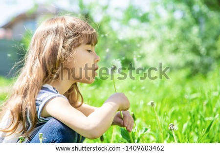 girl blowing dandelions in the air. selective focus. #1409603462
