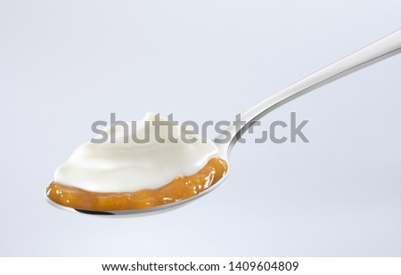 Yogurt on a layer of apricot jam in a spoon on white background #1409604809