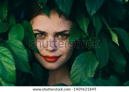 Pretty woman with bright make-up red lips smile green leaves shrub nature glamor rest #1409621849