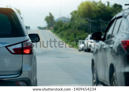 Backside of cars on the road prepare to race or travel on rural asphalt roads by family car. #1409654234